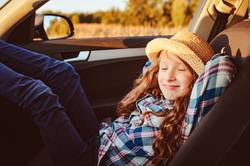 happy child girl relaxing in car during summer road trip