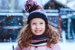 winter portrait of happy child girl playing outdoor