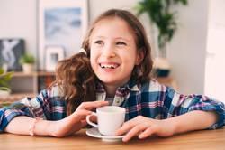 happy kid girl drinking tea for breakfast.