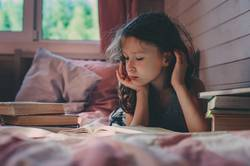 thoughtful kid girl reading book alone