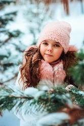 Winter portrait of cute smiling child girl in white coat