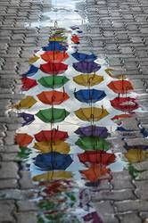 Umbrellas reflection in a puddle