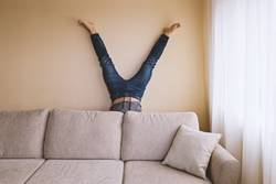 Adult man is standing on his head behind sofa in the room