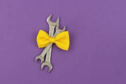 Two crossed wrenches with yellow tie bow on violet background