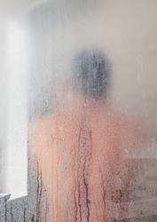 Silhouette of adult man in shower cabin