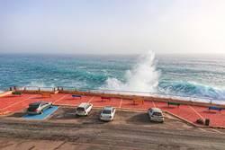 Car parking along coastline with large waves