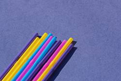 Colored disposable plastic straws on purple background