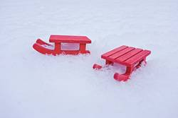 Miniature red sled on white snow