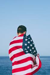 Man from behind wrapped in American Flag against blue sky