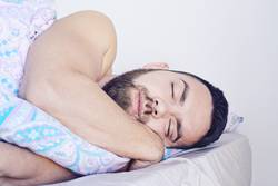 Closeup of sleeping bearded man face in bed