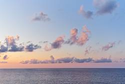 Beautiful sunset sky with cumulus clouds above sea surface