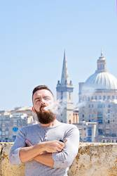 Adult bearded man hispter vaper outdoor against cityscape
