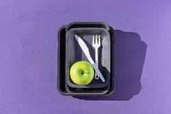 Top view of an empty plastic tray with green apple on purple