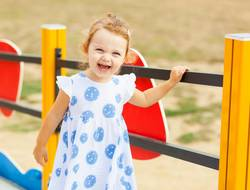 Pretty little girl plays outdoor on a summer day.