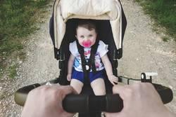 Little baby girl sitting in the pram.