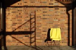 Stuhl mit Decke neben Schatten vom Baugerüst...