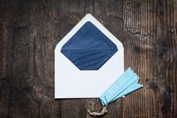 Weisser Briefumschlag auf Holztruhe mit blauen Anhängern