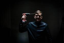 man with electric screwdriver in dark garage
