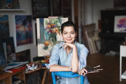 A young smiling brunette woman artist in her studio