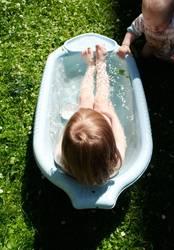 Geschwister baden im Sommer im Garten