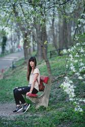 Young woman sitting on a bench in a park in serene pose