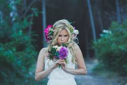 Beautiful blond woman with white dress and flowers in the forest