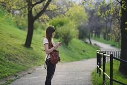 Young woman with long brown hair checking her mobile outdoors