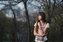 beautiful girl with long brown hair in serene pose in the park