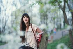 Attractive young woman sitting in a bench in a park
