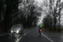 Fahrradfahrer fährt vor einem Auto bei Regen