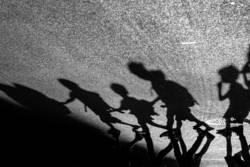 Schattenspiel - Kinder laufen in Reihe über eine Straße