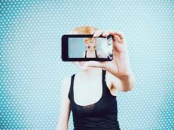 Junge Frau, die ein Selbstporträt mit ihrem Handy nimmt