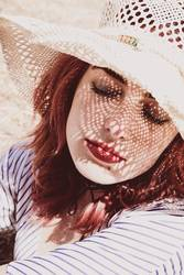 Redhead model protecting herself from sun