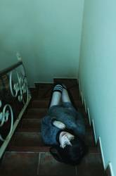 Young creepy woman lying down over a stairs