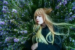 Junge blonde Frau, die über Rosmarinbusch liegt