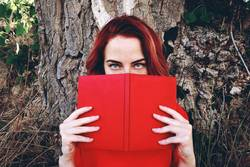 Young redhead woman reading a book