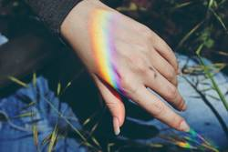 Woman hand with a rainbow projected in it