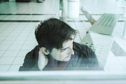 Young man looking throgh a window