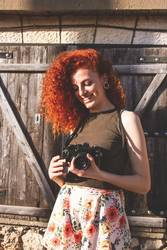 Young redhead photographer woman