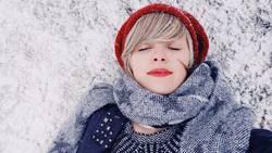 Junge Frau, die sich über einem schneebedeckten Boden hinlegt
