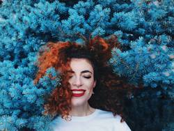 Young and happy redhead woman leaning in blue nature