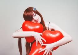 Junge Rothaarigefrau, die Herzballone umarmt