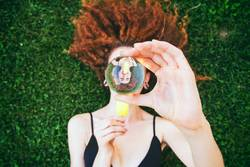 Young woman eating an ice cream viewed through a crystal ball