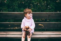 Lovely little girl sitting in a wooden bench