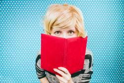 Junge blonde Frau von einem Buch bedeckt