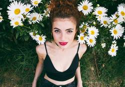 Young woman posing in a garden of daisies