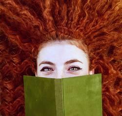 Junge Rothaarigefrau bedecken ihr Gesicht mit einem Buch