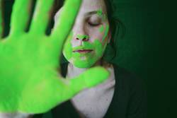 Young woman dirty of green dust behind her hand