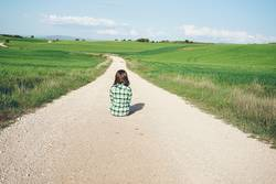 Young woman sitting alone in a rural path