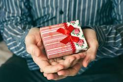 Hände des Mannes, die eine Geschenkbox halten